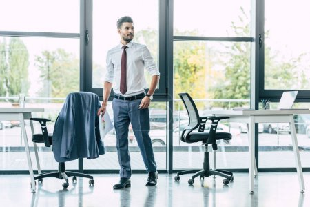 full length view of handsome businessman standing in modern office and holding papers