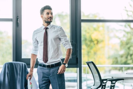 handsome businessman holding documents and looking away in office