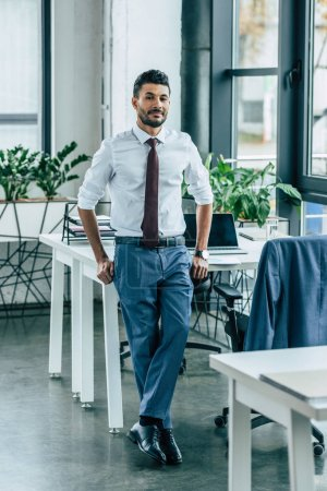 young confident businessman standing near desk and looking at camera