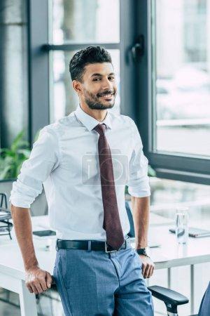 sonriente hombre de negocios de pie cerca del escritorio y mirando a la cámara
