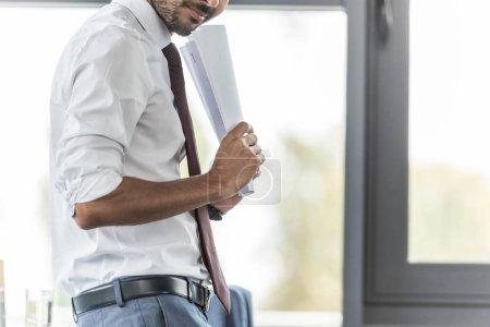 abgeschnittene Ansicht eines lächelnden Geschäftsmannes mit Papieren am Arbeitsplatz