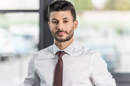 Photo for Young, confident businessman in white shirt looking at camera - Royalty Free Image
