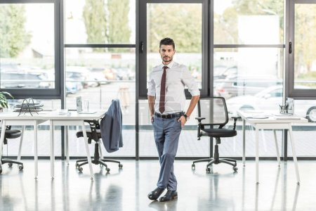 young, confident businessman standing in modern office and looking at camera