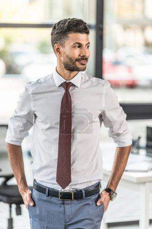 hombre de negocios sonriente cogido de la mano en los bolsillos y mirando hacia otro lado