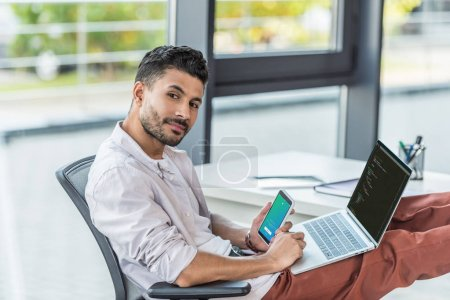 Photo pour Kyiv, Ukraine - 10 octobre 2019 : Young business man holding smartphone with Twitter app on screen and laptop with programming code. - image libre de droit