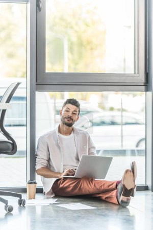 Photo for Young businessman in casual clothes sitting on floor near window and using laptop - Royalty Free Image
