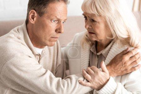 Photo pour Homme âgé atteint de la maladie d'Alzheimer assis près de sa femme inquiète - image libre de droit