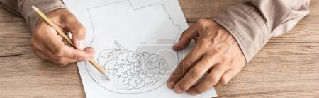 Photo for Panoramic shot of retired man with alzheimer disease drawing human head and brain - Royalty Free Image