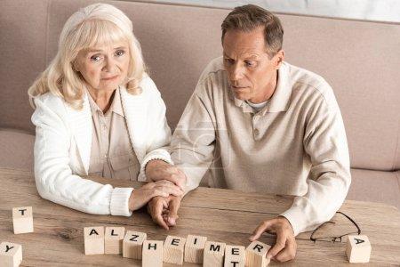 Photo pour Dérangeante une femme âgée assise près de son mari atteinte de dyslexie - image libre de droit