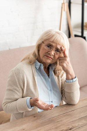 Photo pour Une retraitée atteinte d'alzheimers une ficelle de maladie un rappel d'un doigt humain regarder une caméra alors qu'elle touche un temple - image libre de droit