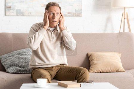 Photo pour Retraité atteint d'une maladie mentale touchant la tête assis sur un canapé - image libre de droit