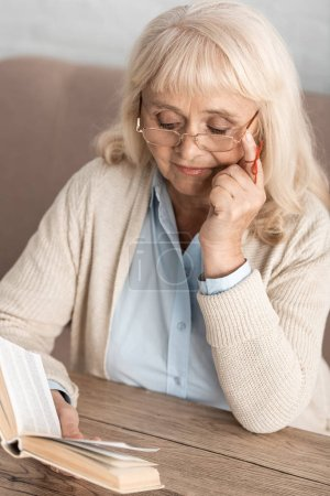 Photo for Senior woman with alzheimers disease string human finger reminder reading book while touching glasses - Royalty Free Image