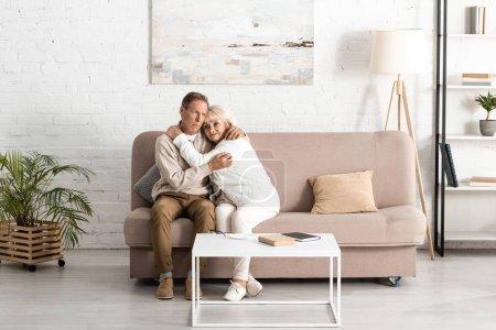 Photo pour Un mari âgé embrassant une femme malade atteinte de maladie mentale alors qu'elle est assise sur un canapé à la maison - image libre de droit