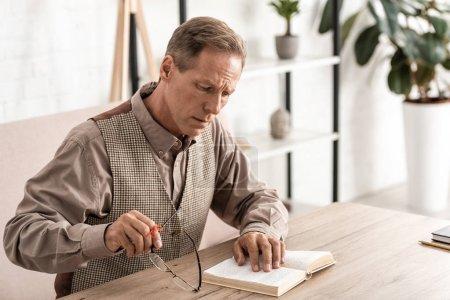 Photo pour Homme dérangé et retraité atteint de la maladie d'Alzheimer ficelle doigt humain rappel lecture d'un livre et port de lunettes - image libre de droit