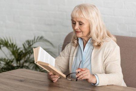 Photo pour Femme âgée atteinte de la maladie d'Alzheimer ficelle doigt humain rappel lecture d'un livre et port de lunettes - image libre de droit