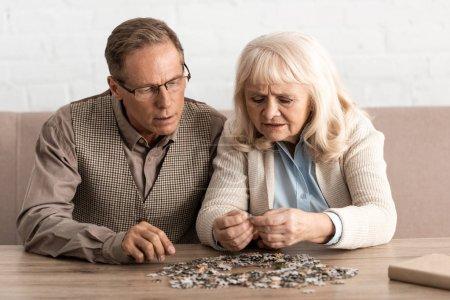 Photo pour Centre d'intérêt sélectif d'un couple de personnes âgées atteintes d'une maladie mentale pièces de casse-tête - image libre de droit