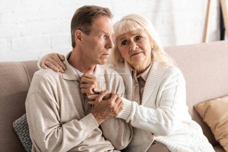 Photo pour Une femme âgée triste embrassant un mari atteint de maladie mentale à la maison - image libre de droit
