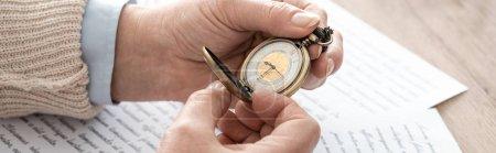 Photo pour Photo panoramique d'un homme âgé tenant une montre de poche près de journaux avec lettres - image libre de droit