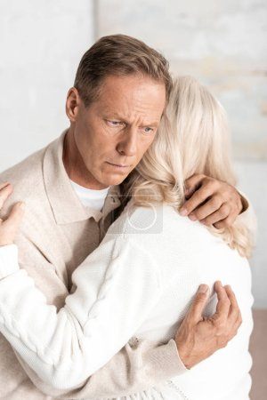 back view of retired woman hugging husband with mental illness at home