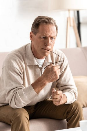 Photo for Thoughtful retired man with memory loss sitting on sofa and holding glasses - Royalty Free Image