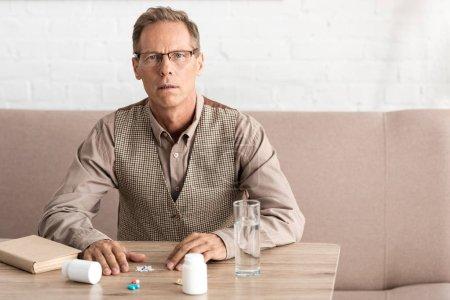 Photo pour Retraité atteint d'une maladie mentale assis près d'une pilule sur la table - image libre de droit