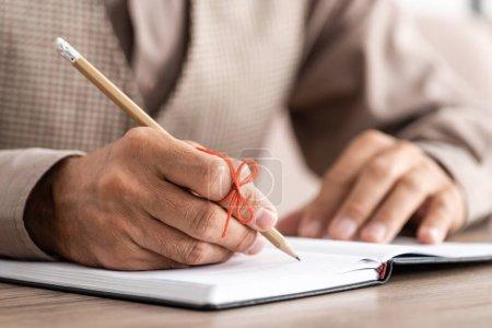 Photo pour Crochet vue d'un retraité atteint de la maladie d'Alzheimer ficelle doigt humain rappel écriture dans un carnet - image libre de droit