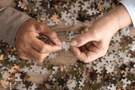 Photo for Cropped view of retired couple holding jigsaw - Royalty Free Image