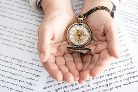 Photo pour Vue du dessus de la femme âgée tenant montre de poche près des papiers avec des lettres - image libre de droit