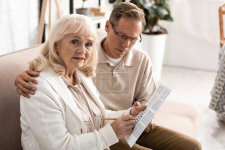 Photo pour Aîné assis près d'une femme malade avec alzheimer tenant du papier avec des lettres et un crayon - image libre de droit