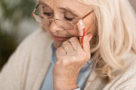 Photo pour Focus sélectif of seniors woman with alzheimers disease string human finger reminder touching glasses - image libre de droit
