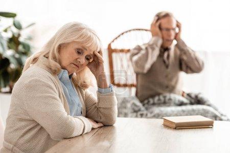 Photo pour Focus sélectif of upset retired woman sitting near husband with mental illness - image libre de droit