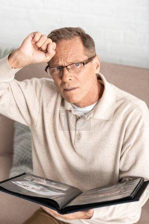 Photo pour Bouleversé homme âgé dans des lunettes tenant album photo - image libre de droit