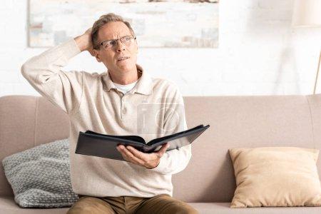 Photo pour Confus homme âgé dans des lunettes tenant album photo tout en étant assis sur le canapé - image libre de droit