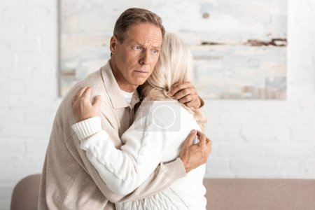 Photo for Senior man with alzheimer disease hugging wife at home - Royalty Free Image