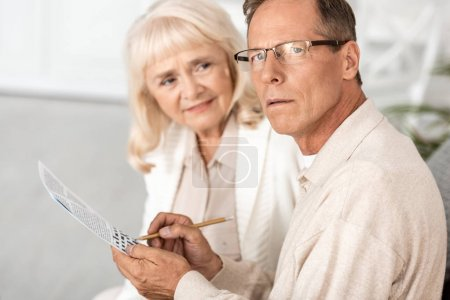 Photo pour Focus sélectif of sick senior man with alzheimer holding pencil near crossword and wife - image libre de droit