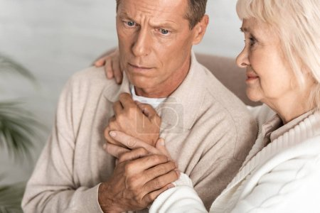 Photo for Sad retired woman hugging husband with alzheimer illness at home - Royalty Free Image