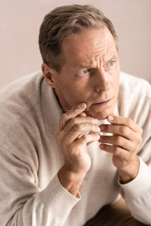 Photo for Overhead view of pensive senior man with memory loss thinking and touching face - Royalty Free Image