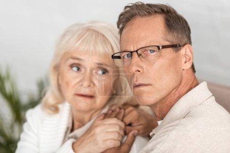 Photo pour Foyer sélectif de l'homme âgé malade dans des lunettes tenant la main avec sa femme - image libre de droit