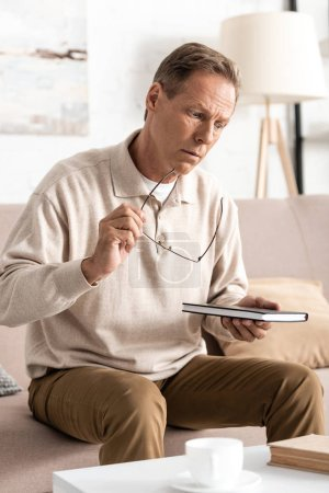 sad senior man sitting on sofa and holding notebook