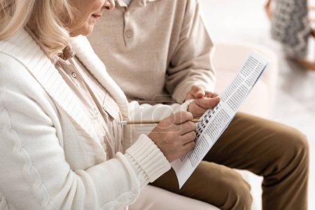 Photo pour Crochet vu d'un homme âgé assis avec sa femme en train de résoudre des mots croisés - image libre de droit