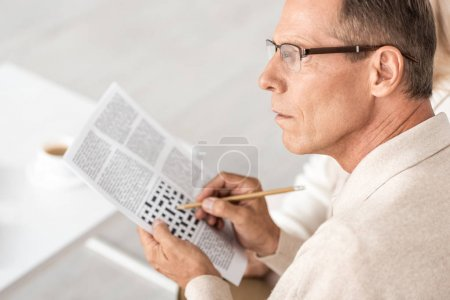 Photo pour Focus sélectif of senior man in glasses holding pencil near crossword in newspaper - image libre de droit