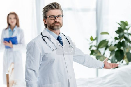 Photo for Selective focus of doctor in white coat pointing with hand in hospital - Royalty Free Image