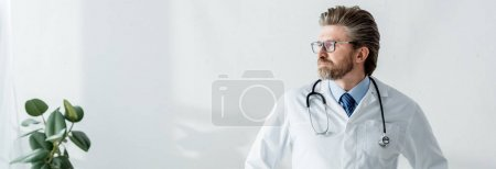 Photo pour Panoramic shot of handsome doctor in white coat looking away in hospital - image libre de droit