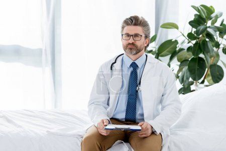Photo for Handsome doctor in white coat sitting on bed and holding clipboard in hospital - Royalty Free Image