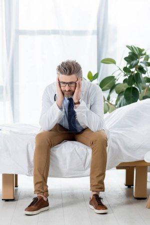 Photo pour Médecin triste en manteau blanc assis au lit et regardant vers le bas à l'hôpital - image libre de droit