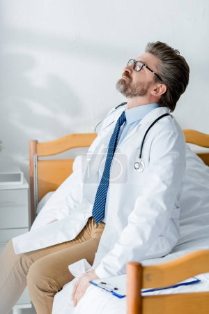 handsome doctor in white coat sitting on bed and looking up in hospital