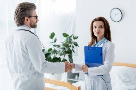 Photo pour Médecin en manteau blanc et son collègue serrant la main à l'hôpital - image libre de droit