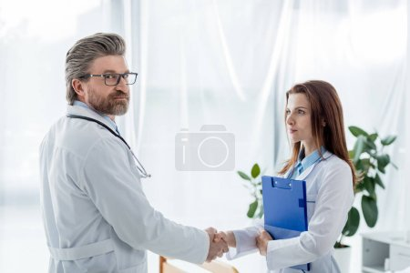 Photo pour Doctor in white coat and his colleague shaking hands in hospital - image libre de droit