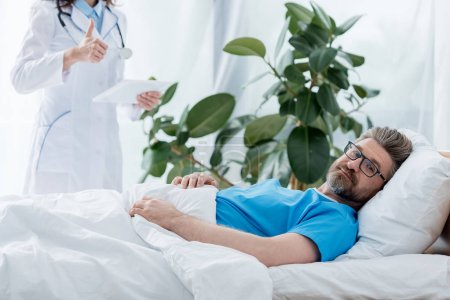 Photo pour Cropped view of doctor in white coat showing like and holding digital tablet and patient lying in bed in hospital - image libre de droit