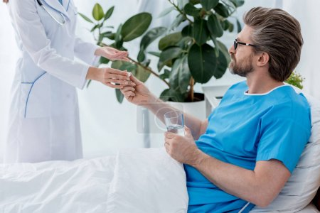 Photo for Cropped view of doctor in white coat giving pill to patient in hospital - Royalty Free Image